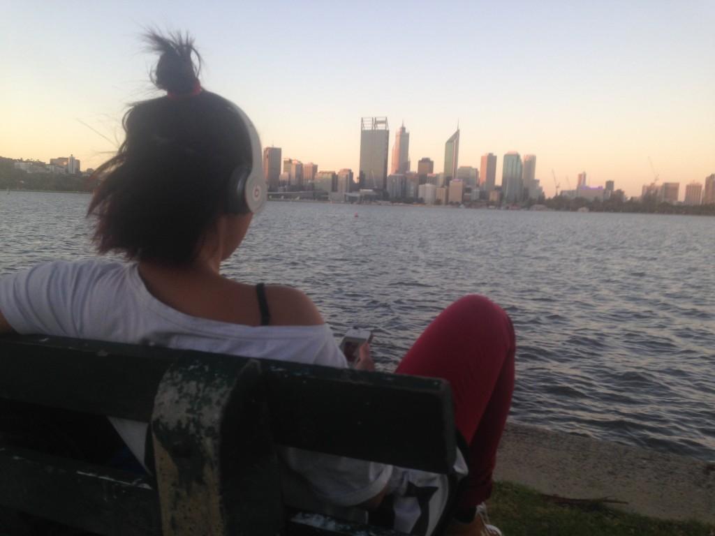 Sonia in un momento di relax, musica nelle orecchie e lo skyline di Perth sullo sfondo